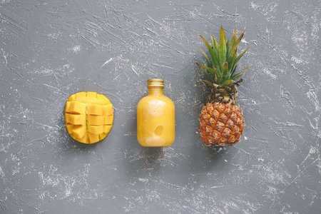 Fresh yellow smoothie with pineapple and mango on gray table, top view. Фото со стока