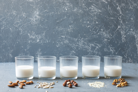 Different types of vegan non-dairy milk in glasses on wooden background with copy space.