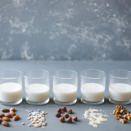 Different kinds of vegan non-dairy milk in glasses on wooden background with copy space. Stock Photo
