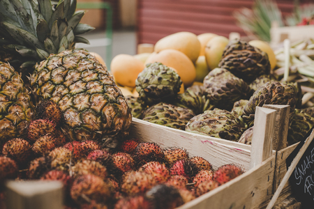 Exotic tropical fruits. Rambutan, pineapple and sugar apples at street food market.