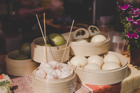 Asian steamed buns in bamboo steamers at street food market. Stock Photo