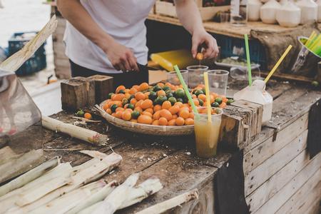 Man making fresh juice from kumquats at street food market.