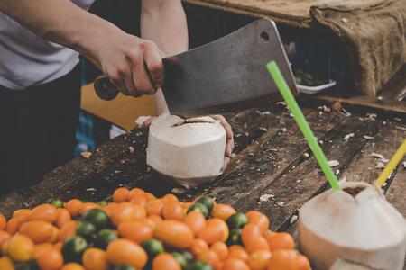 Man cutting fresh coconut at street food market. Stock Photo