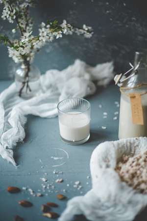 Vegan non-dairy almond milk with almond pulp on wooden background.
