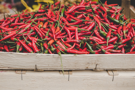 Red chilli peppers in wooden box at street food market.