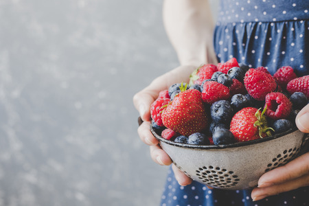 Hands holding fresh juicy berries. Summer background with copy space