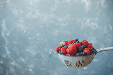 Mix of washed fresh juicy berries in colander. Background with copy space
