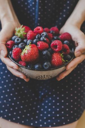 Organic fresh harvested berries. Hands holding fresh juicy berries, closeup