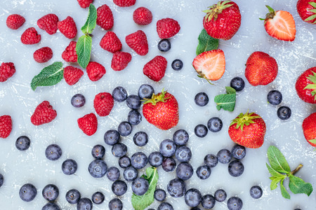 Mix of fresh juicy berries on blue background, top view