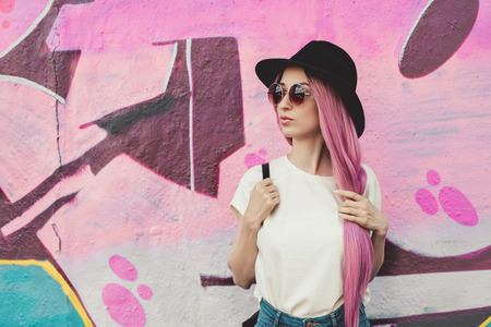 Beautiful stylish young hipster woman with long pink hair, hat and sunglasses on the street. Stock Photo