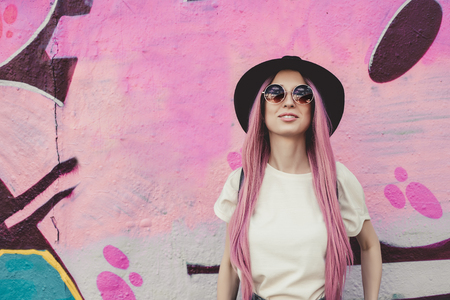 Happy stylish young hipster woman with long pink hair, hat and sunglasses on the street.