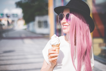 Happy young hipster woman with long pink hair, hat and sunglasses eating ice cream outdoors