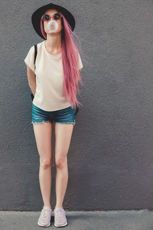 Stylish young hipster woman with long pink hair blowing a bubble with bubble gum. Фото со стока