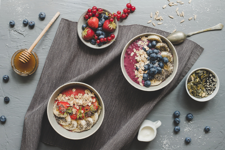 Healthy delicious smoothie bowls with fruits, berries and seeds. Top view
