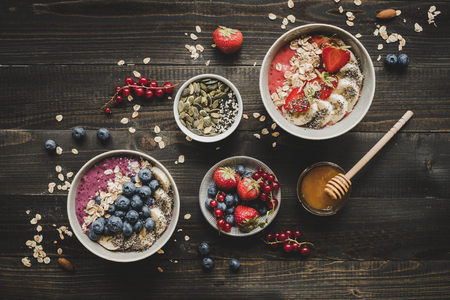 Helthy breakfast. Delicious smoothie bowls with fruits, berries and seeds on the wooden background.