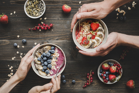 Eating helthy breakfast. Delicious smoothie bowls with fruits, berries and seeds on the wooden background