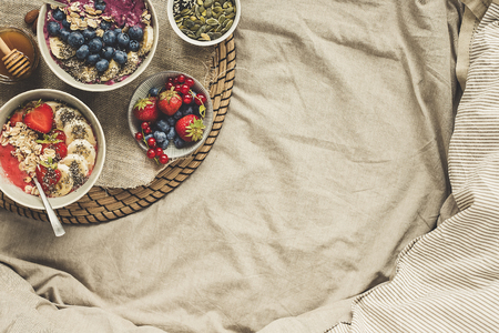 Helthy breakfast in bed. Delicious smoothie bowls with berries, fruits and seeds, top view. Background with copy space