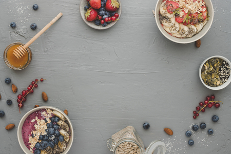 Healthy delicious smoothie bowls with fruits, berries and seeds. Background with copy space, top view