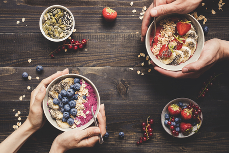 Helthy breakfast. Hands holding delicious smoothie bowls with fruits, berries and seeds on the wooden background