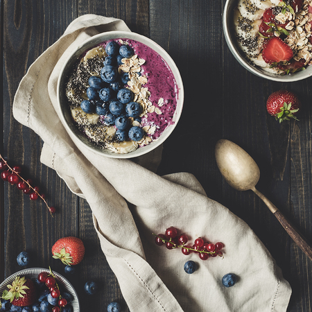 Delicious smoothie bowl with blueberries, banana and chia seeds on the wooden background. Top view Фото со стока