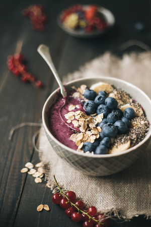 Delicious smoothie bowl with blueberries, rolled oats and chia seeds on the wooden background Фото со стока