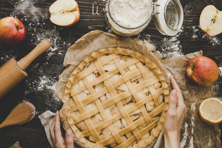 Cooking apple pie. Hands holding apple pie ready to be baked. Apple pie ingredients on wooden table Stock Photo