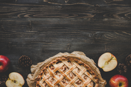 Traditional homemade apple pie on the wooden table with copy space. Top view