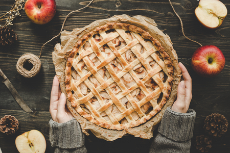 Hands holding homemade delicious apple pie on the wooden table. Top view. Stock Photo