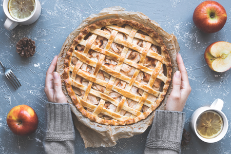Hands holding homemade delicious apple pie on the blue rustic table. Top view. Stock Photo