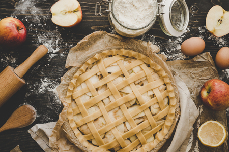 Cooking apple pie. Homemade apple pie ready to be baked. Apple pie ingredients on wooden table. Stock Photo