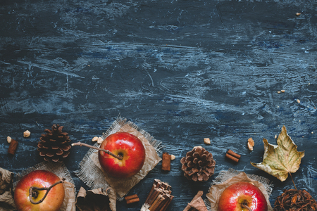 Autumn background with copy space. Delicious caramel apples with autumn decoration, top view.