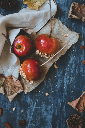 Autumn background top view. Delicious caramel apples with twig sticks and autumn decoration. Stock Photo