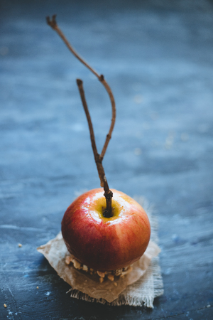Old fashioned caramel apple with brunch sticks and nuts. Selective focus. Stock Photo