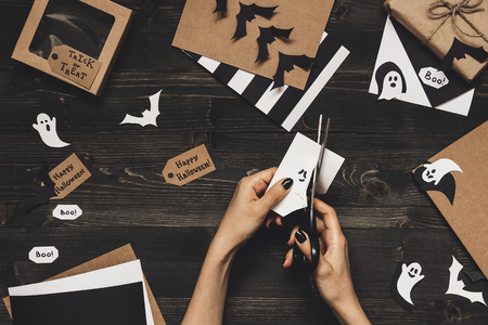 Halloween preparation. Hands making halloween cards and decoration using craft paper. Stock Photo