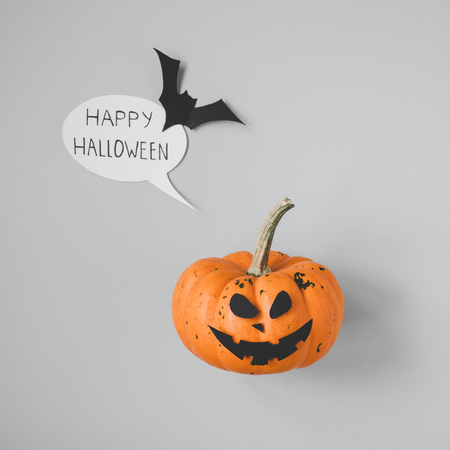 Happy halloween. Halloween pumpkin with speech bubble and bat on gray background.