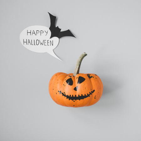 Happy halloween. Funny halloween pumpkin with speech bubble and bat on gray background.