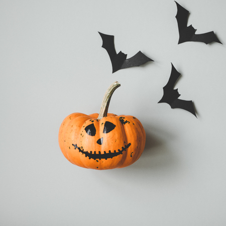 Happy halloween. Funny halloween pumpkin with paper bats on gray background.
