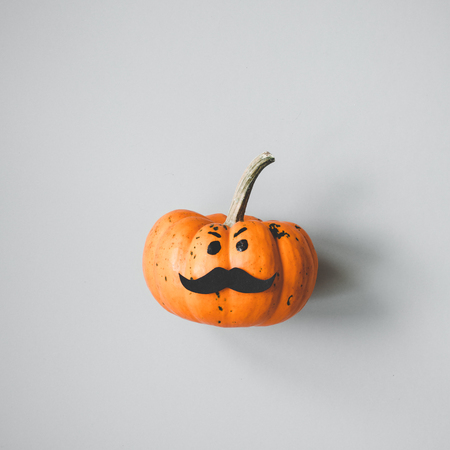 Halloween pumpkin Jack o Lantern with mustache on gray background. Stock Photo