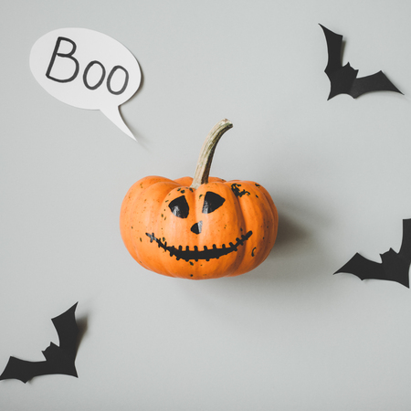 Happy halloween. Funny halloween pumpkin with speech bubble and paper bats on gray background. Stock Photo