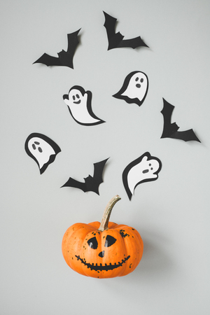Happy halloween. Funny halloween pumpkin with paper bats and ghosts on gray background. Stock Photo