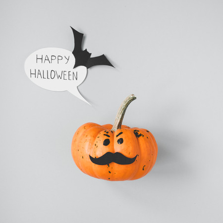 Halloween pumpkin Jack o Lantern with mustache and speech bubble on gray background.