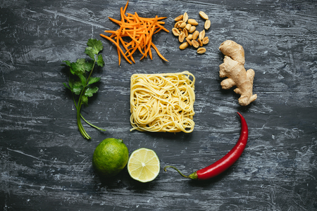 Dried asian noodles with lime, nuts, cilantro and vegetables on wooden background. Top view.