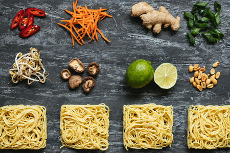 Ingredients for asian dish. Dried asian noodles with lime, nuts, cilantro and vegetables on wooden background. Top view. Stock Photo