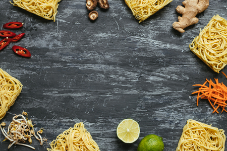 Dried asian noodles with different ingredients on wooden background with copy space. Top view. Stock Photo