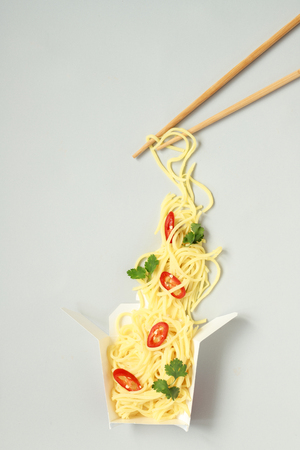 Asian food with chopsticks. Asian egg noodles with chili and cilantro in take away paper box, top view. Stock Photo
