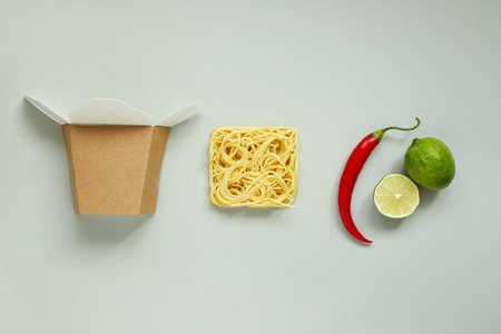 Asian food. Asian dried noodles with lime, chili and paper box, top view.