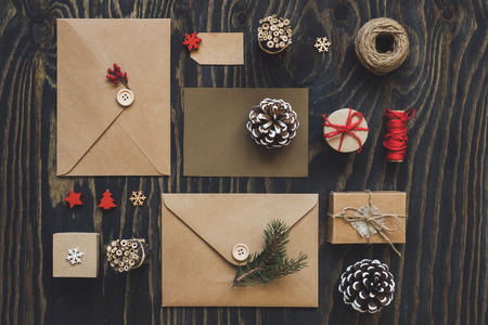 Christmas package. Christmas cards, gifts and christmas decoration on wooden table, top view.