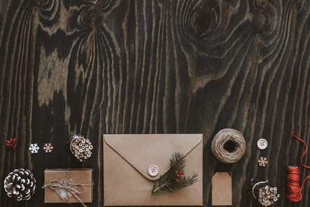 Christmas package. Christmas cards, gifts and christmas decoration on wooden table, top view. Copy space Stock Photo