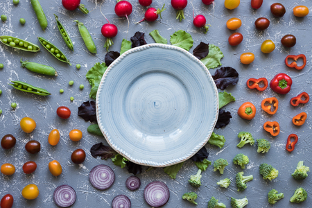 Fresh organic vegetables with blue plate on table. Green peas, broccoli, onion, tomato and radish top view