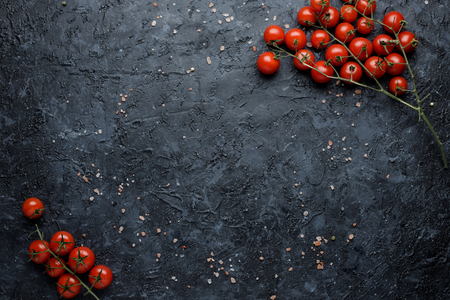 Branch of ripe cherry tomatoes on black background, top view. With copy space.